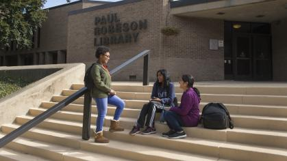 Students talk on the steps of the Paul Robeson Library at Rutgers University-Camden